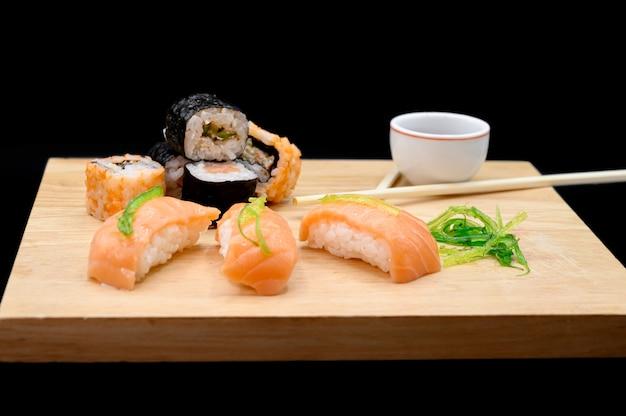 Sushi na mesa de madeira em fundo preto isolado.