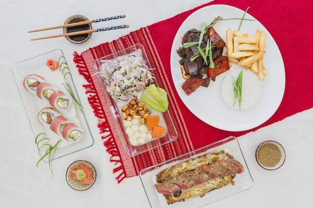 Sushi nikkei, lomo saltado, atum, ceviche e molho de soja em uma mesa branca