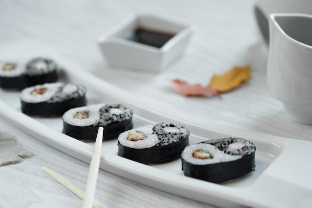 Sushi preto com molho no prato