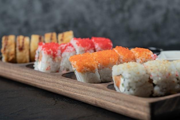 Sushi quente definido em uma placa de madeira com ingredientes misturados.