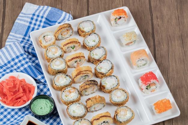 Sushi quente frito com molho de soja, wasabi e gengibre em uma toalha xadrez azul.