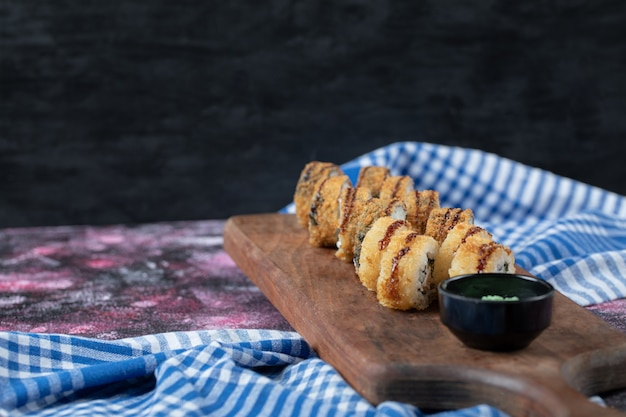 Sushi quente frito rola em uma placa de madeira com molho de wasabi.