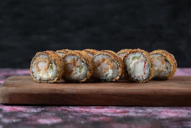 Sushi quente frito rola em uma placa de madeira.