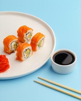 Sushi rola em um prato branco sobre um azul.