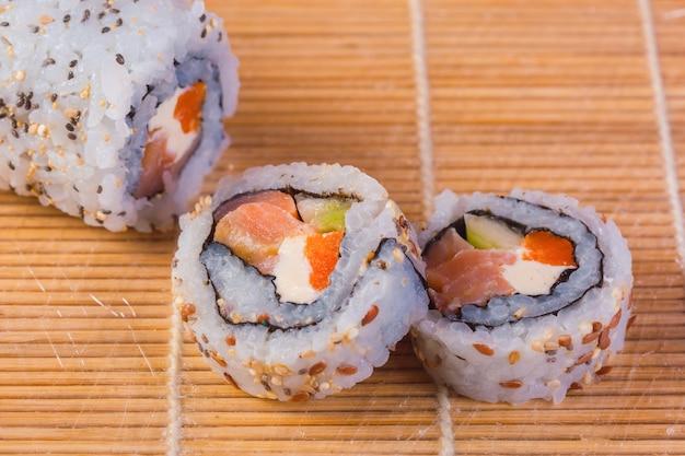 Sushi roll com arroz, salmão, sementes. menu de sushi. culinária japonesa.