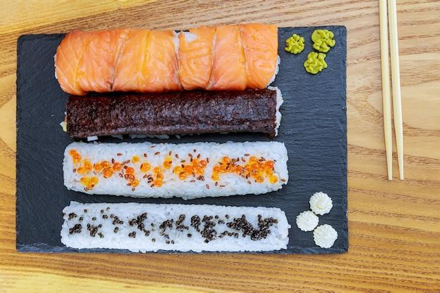 Sushi roll com salmão, caviar vermelho e caviar preto em uma placa preta sobre uma superfície de madeira. mulher usando tapete de bambu para fazer sushi caseiro