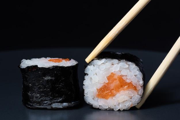 Sushi roll com salmão em um fundo preto pauzinhos de madeira seguram sushi roll