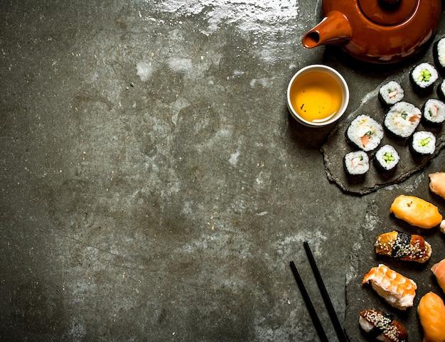 Sushi roll de comida japonesa e uma xícara de chá na mesa de pedra