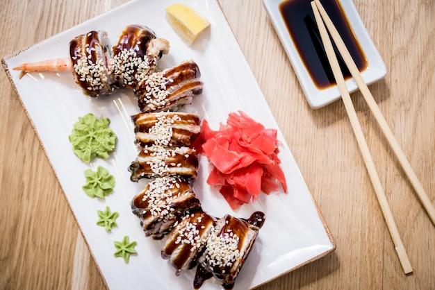 Sushi roll dragão verde com abacate, ell, wasabi e gengibre.