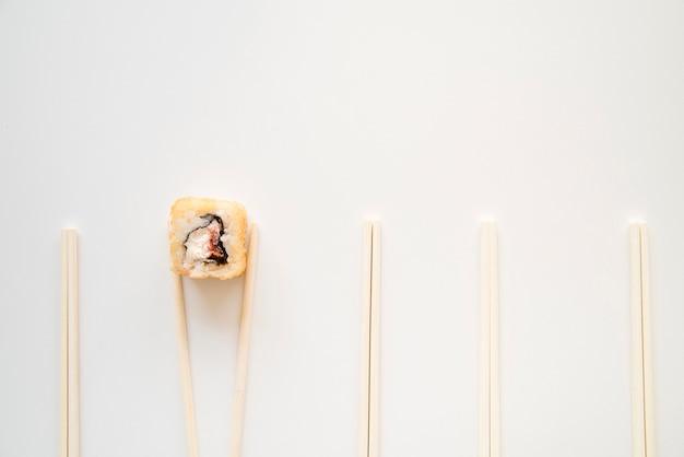 Sushi roll entre pauzinhos com cópia-espaço