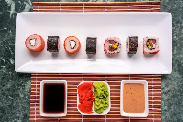Sushi roll feito na hora com molho de soja, molho de gergelim, wasabi e gengibre em conserva. cozinha tradicional japonesa.