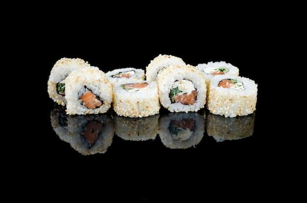 Sushi roll filadélfia em gergelim com salmão no fundo preto