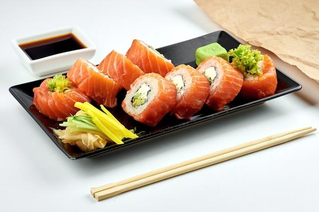 Sushi roll japonês clássico - filadélfia com salmão, cream cheese e abacate, servido em prato preto. superfície branca