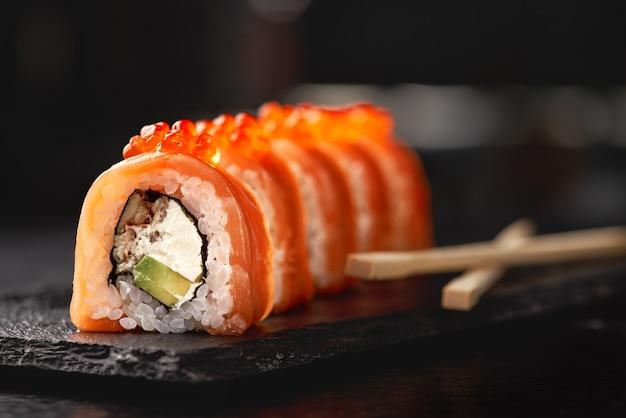 Sushi roll maki futo comida japonesa em uma placa de pedra preta nas mãos de um garçom.