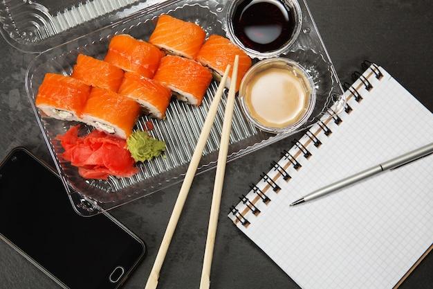 Sushi roll na filadélfia. rolo filadélfia em um recipiente plástico descartável para alimentos. conceito de almoço de negócios
