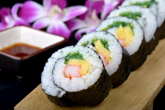 Sushi roll ou maki japonês com ovo de algas marinhas e kani cortados e colocados numa placa de madeira.