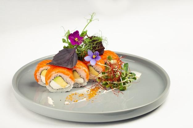 Sushi roll philadelphia com abacate decorado com ervas em um prato, sushi japonês clássico. comida tradicional japonesa com maki.