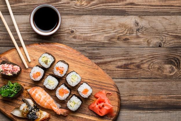 Sushi, rolos e especiarias no fundo marrom claro de madeira