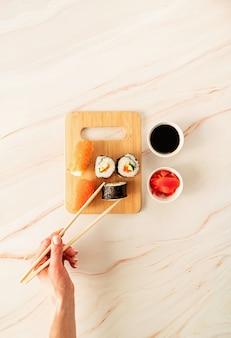 Sushi salmão definido na tábua de madeira. mão de uma mulher segurando o rolo de sushi com palitos. postura plana