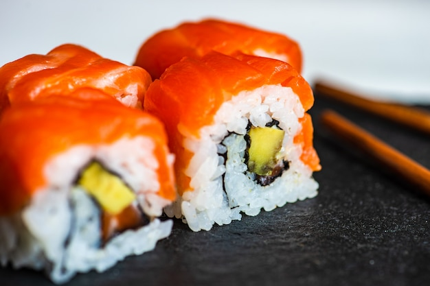 Sushi set sashimi e rolos de sushi servidos em ardósia de pedra