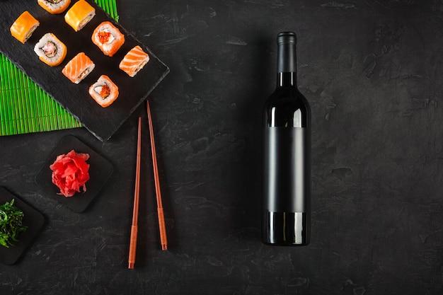Sushi set sashimi e sushi rolls, garrafa de vinho e um copo servido na ardósia de pedra