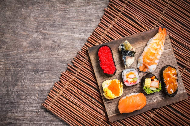 Sushi set sashimi e sushi rolos servidos em ardósia de madeira