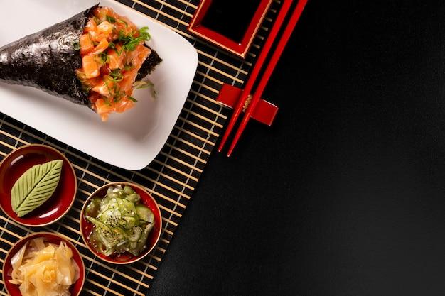 Sushi temaki de salmão na chapa branca em fundo preto.