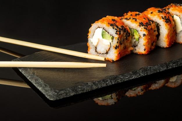 Sushi tradicional e pauzinhos da filadélfia com salmão, abacate e queijo
