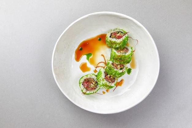 Sushi uramaki com peixe, alga verde com molho em uma tigela branca