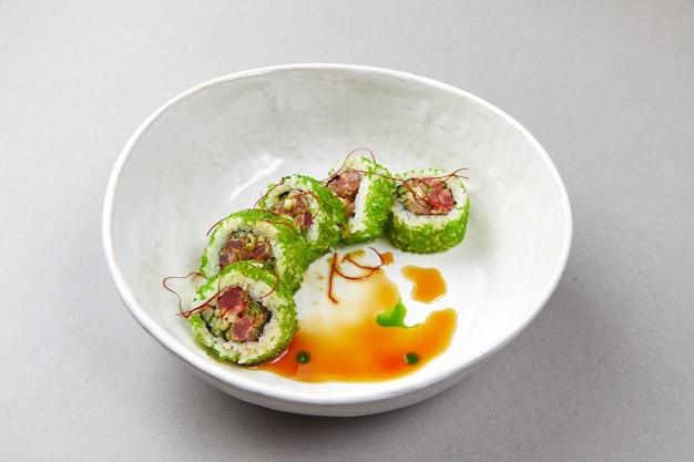 Sushi uramaki com peixe, algas verdes com molho