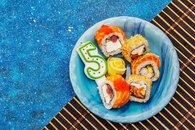 Sushi variado com uma vela em forma do número cinco. conceito de aniversário infantil