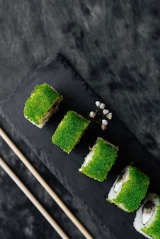 Sushi verde com close-up em superfície preta