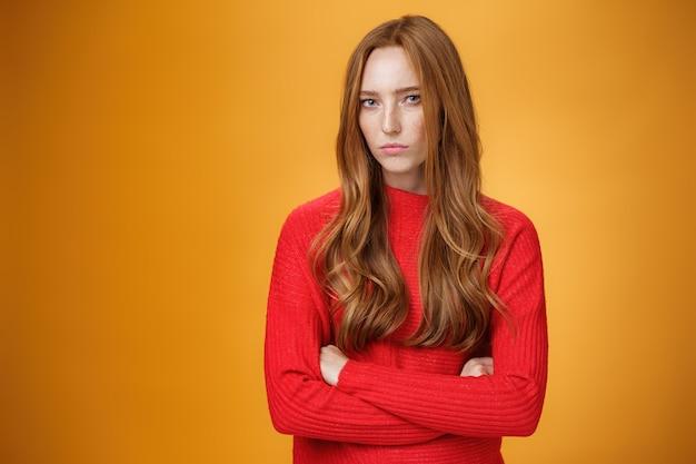 Suspeita, intensa e defensiva, menina ruiva em pose passivo-agressiva fazendo beicinho e carrancuda olhando com descrença e desdém para a câmera, ofendida contra um fundo laranja