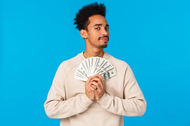 Suspeito e duvidoso jovem pensativo cara rico afro-americano segurando muito dinheiro, prêmio de loteria, tem dinheiro e olhando com descrença ou câmera cética, parte relutante, em pé azul