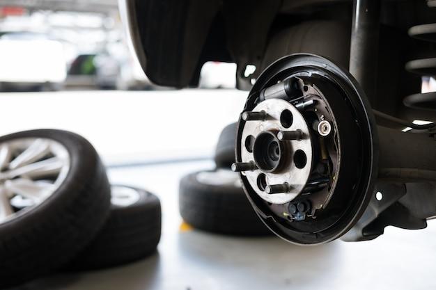 Suspensão do carro e rolamento do cubo de roda na manutenção do serviço de auto. carro elevador hidráulico, à espera de substituição de pneus na garagem. conceito de roda perfurada