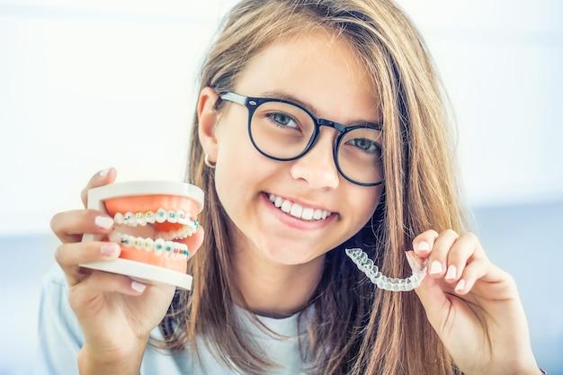 Suspensórios invisíveis segurados por uma jovem sorridente