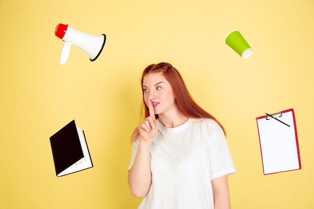 Sussurrando segredos. retrato de mulher jovem caucasiana em fundo amarelo do estúdio, muitas tarefas. como gerenciar o tempo certo. conceito de trabalho, negócios, finanças, freelance, autogestão, planejamento.