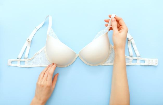 Sutiã branco em mãos femininas. lingerie de renda branca sobre fundo azul. postura plana com sutiã de renda.