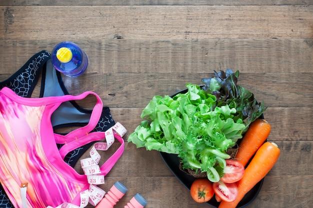 Sutiã esportivo de mulher e alimentos saudáveis em fundo de madeira com copyspace