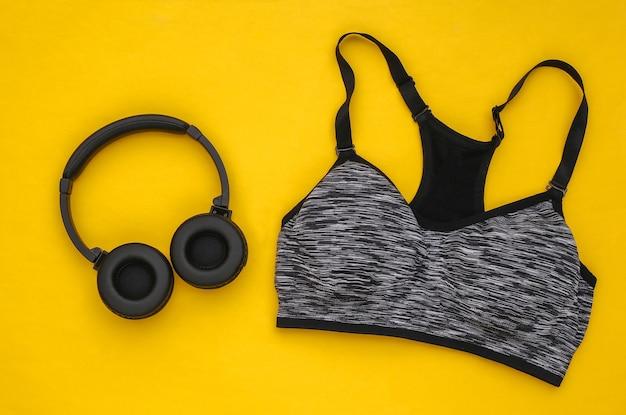 Sutiã esportivo e fones de ouvido estéreo em fundo amarelo. esporte e preparação física. preparando-se para o treinamento. vista do topo. postura plana