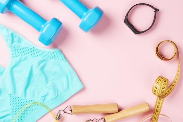 Sutiã esportivo, halteres, fita métrica, pular corda e rastreador de aptidão em um fundo rosa