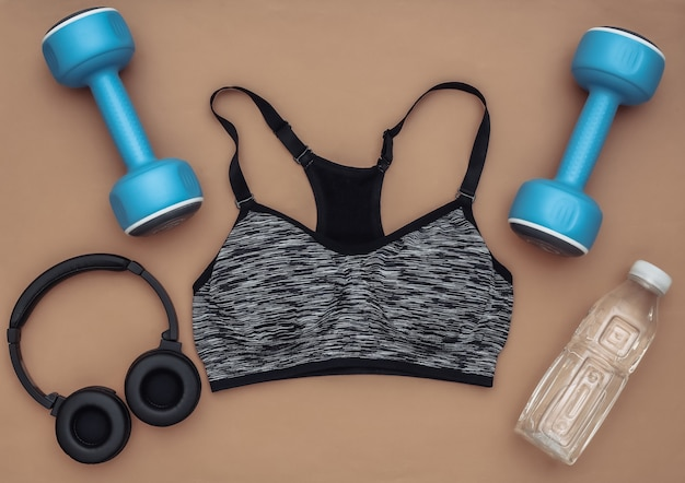 Sutiã esportivo, halteres, garrafa de água e fones de ouvido estéreo em fundo marrom. esporte e preparação física. vista do topo. postura plana