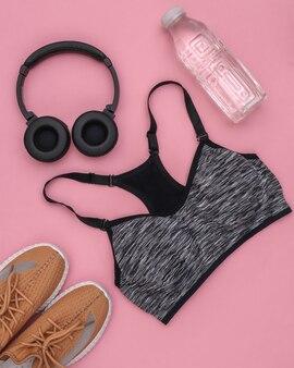 Sutiã esportivo, halteres, garrafa de água e fones de ouvido estéreo em fundo rosa. esporte e preparação física. vista do topo. postura plana