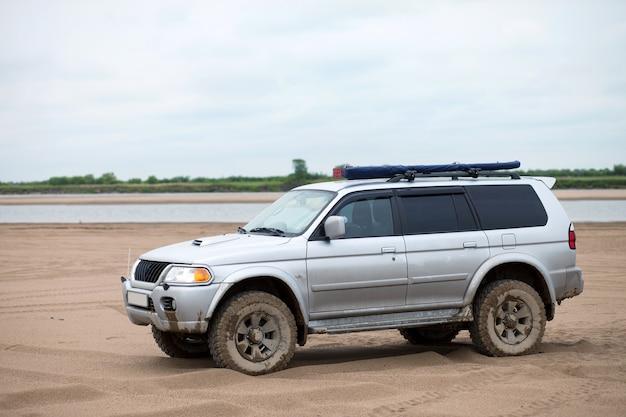 Suv 4x4 com pneus de lama na margem arenosa de um rio