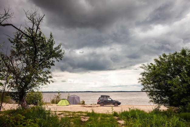Suv preto com caixa na cobertura perto de acampamento no rio.