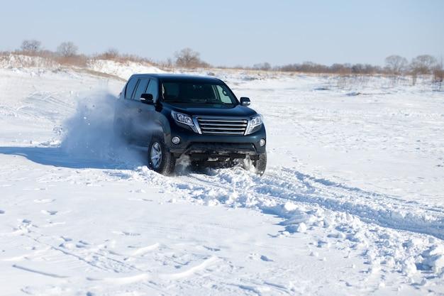 Suv preto viajando na neve