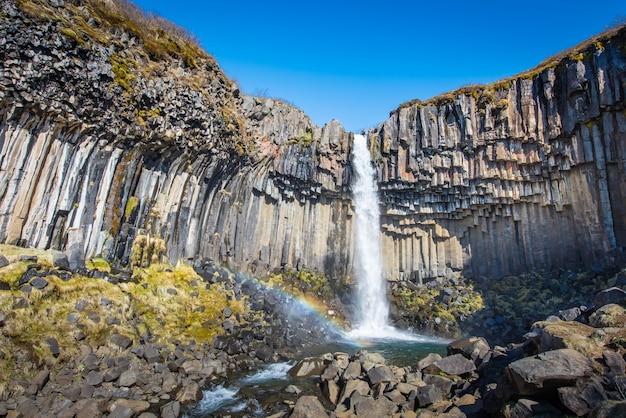 Svartifoss no meio-dia sem clounds na islândia com arco-íris