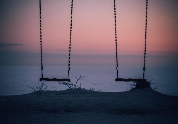 Swing no inverno no lago ao pôr do sol