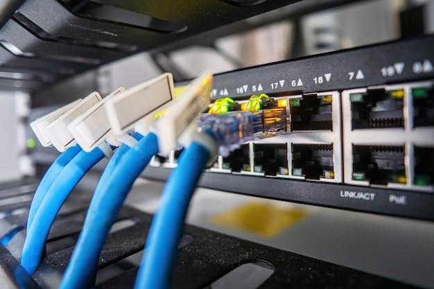 Switch de rede e cabo ethernet no gabinete do rack tecnologia de conexão de rede e tem um led de status