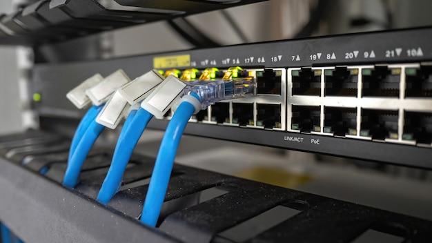 Switch de rede e cabo ethernet no gabinete do rack tecnologia de conexão de rede